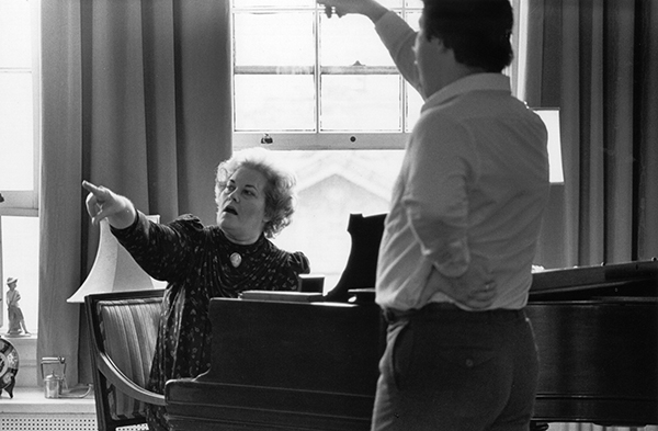 woman at piano teaching student to sing